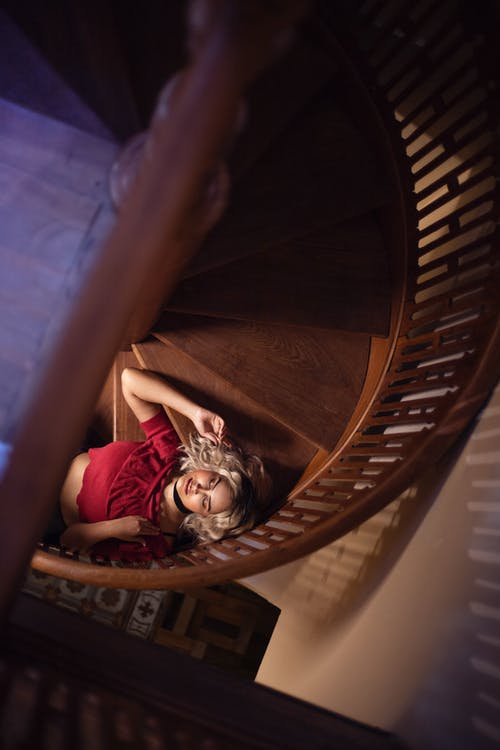 Woman in Red Shirt Lying on Brown Wooden Spiral Staircase