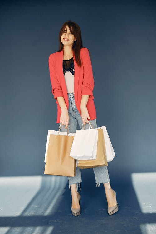 Stylish young woman with paper shopping bags