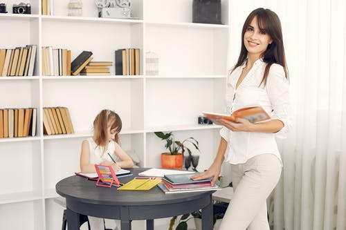 Cheerful woman in formal white shirt standing with textbook in hands near table with various school items and abacus and looking on camera while little adorable child writing in notebook with pencil in light room with bookshelf