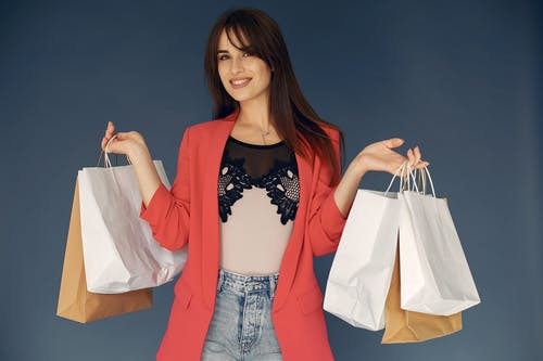 Stylish female shopper in trendy outfit with jacket and jeans standing against gray background with paper bags and smiling looking at camera