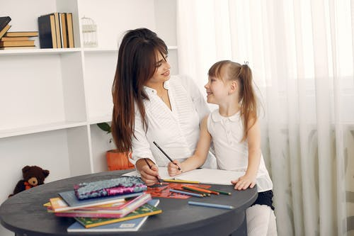 Cheerful schoolchild practicing handwriting at home with tutor