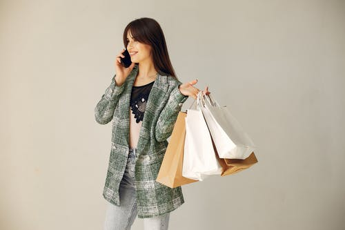 Attractive young woman with shopping bags during phone call