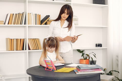 Smart little girl sitting at table with abacus and textbooks and writing in diary with pencil with content young home teacher in white shirt standing behind during early home education
