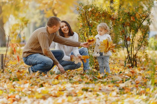 Happy family with little daughter in autumn park