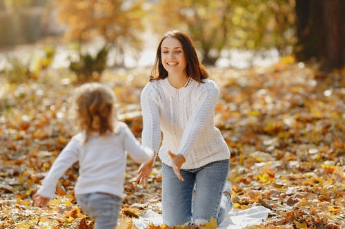 Happy young mother and daughter having fun in autumnal park