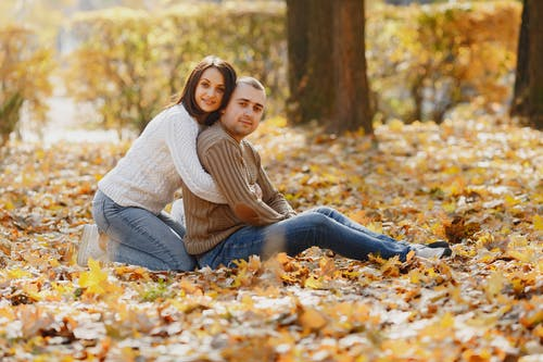 Side view of cheerful girlfriend in white sweater sitting on lawn with fallen yellow leaves hugging from back handsome boyfriend in brown sweater during romantic date while looking at camera