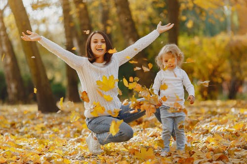Playful mother and daughter having fun in autumn park