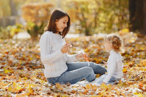 Side view of cheerful young woman in warm sweater smiling and sitting on lawn with fallen leaves face to face with cute girl with curly hair while blowing bubbles in daytime