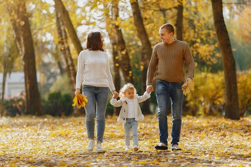 Happy family walking on alley in autumn park