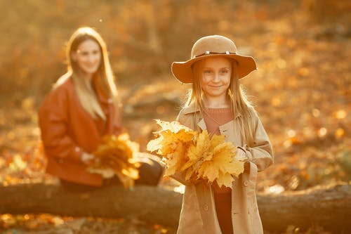 Cheerful young girl with long hair in trendy outerwear and hat holding bunch of yellow leaves and young woman sitting on tree with bunch of autumn leaves in autumn park