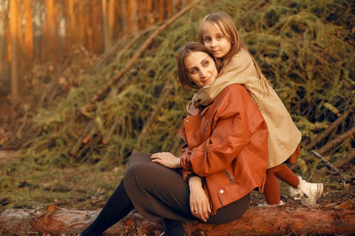 Happy mother with daughter in autumn forest