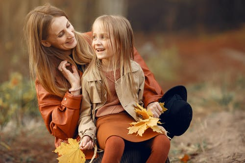 Delighted smiling daughter in stylish brown skirt and beige trench coat sitting on mother laps with yellow maple leaves while spending day together in autumn park
