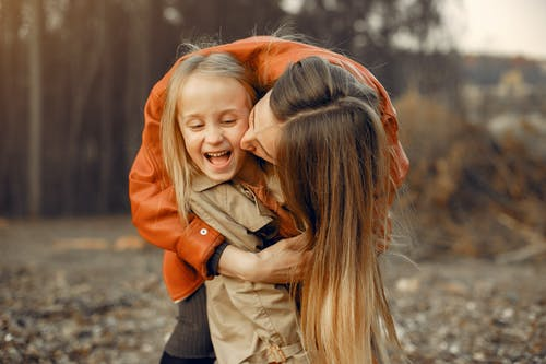 Tender mother hugging and kissing daughter in forest