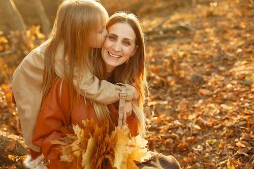 Happy daughter kissing mothers cheek in autumn sunset park