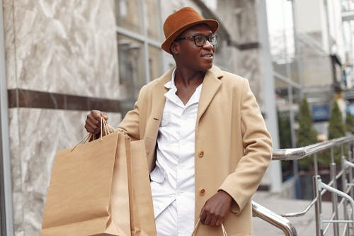 Cheerful black man with shopping bags on street