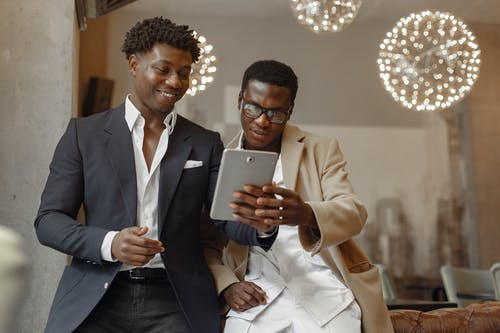 Happy businessmen browsing tablet in modern workspace