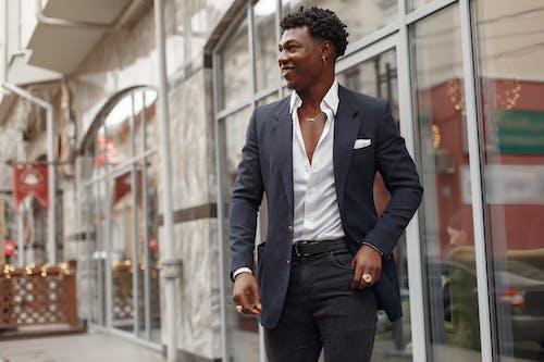 Confident stylish man in elegant suit walking along street