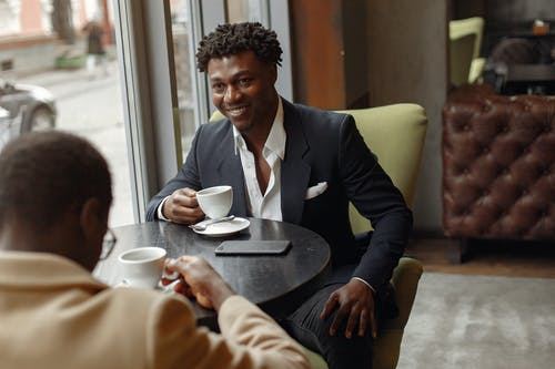 Cheerful smiling African American males in elegant formal suits sitting at table in contemporary cafeteria and discussing business strategy in daylight