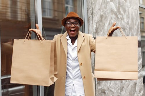 Excited man showing shopping bags near marble wall