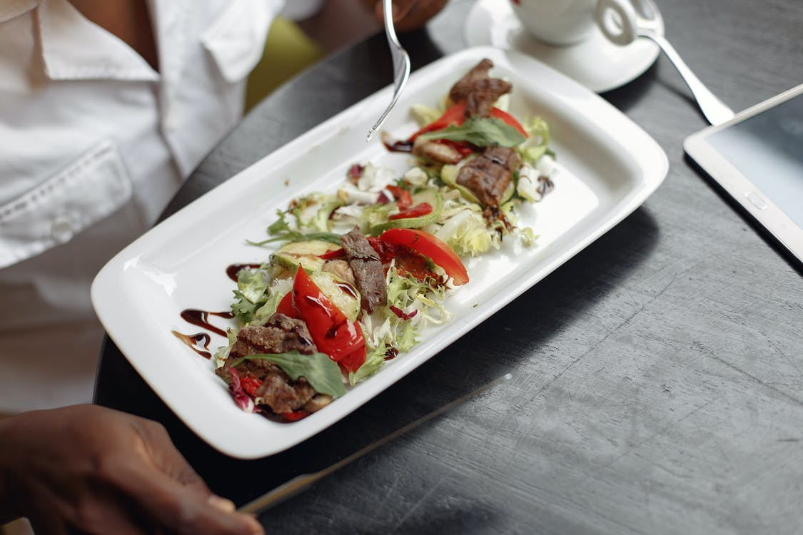 From above of crop anonymous person in white shirt eating yummy healthy appetizer with mix salad leaves and grilled beef topped with capsicum and balsamic vinegar sauce on white plate