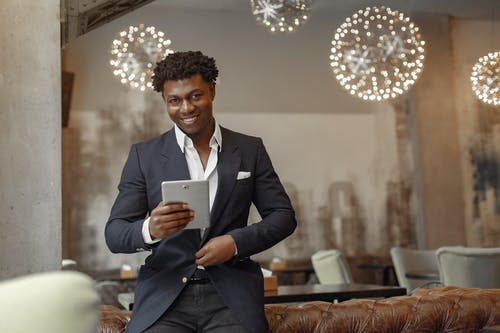 Positive successful black businessman in elegant formal outfit leaning on leather sofa and browsing tablet while unbuttoning jacket button in modern cafe