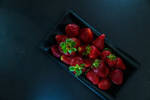 Plate of fresh strawberries in daylight