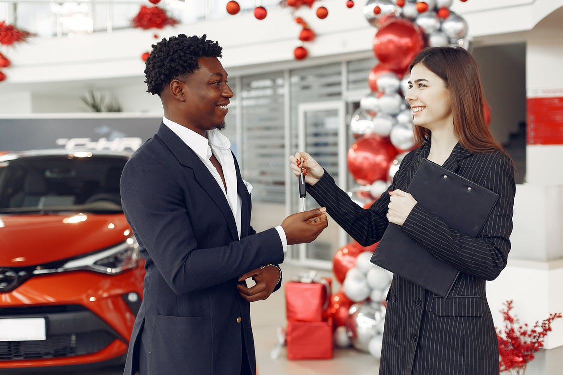 Cheerful young woman dealer passing car keys to client