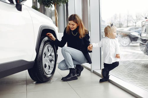 Happy woman with daughter checking car wheel in car showroom