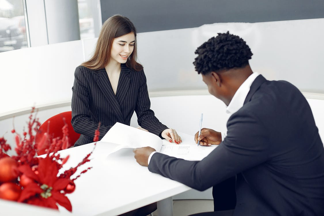 Diverse buyer and agent signing papers