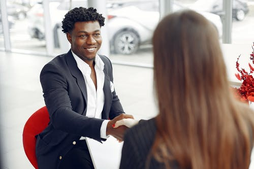 Cheerful happy African American customer in formal elegant suit shaking hands with female dealer after signing papers while smiling and looking at each other