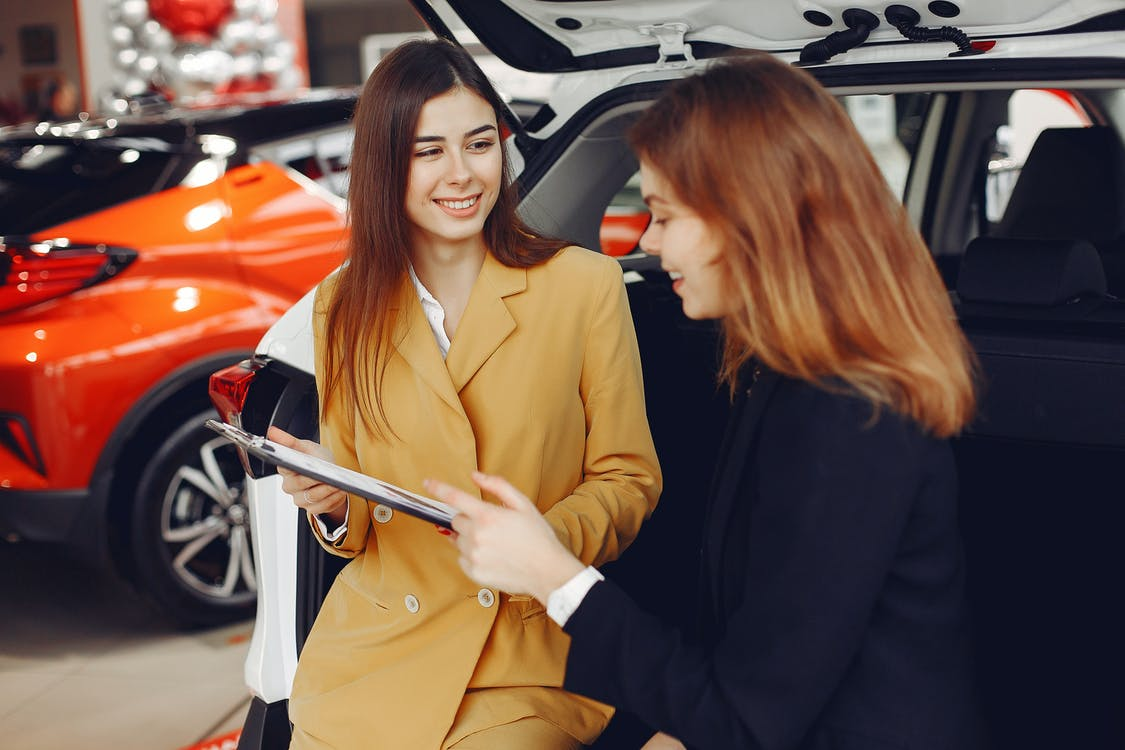 Friendly Car Dealer Showing the Contract to a Customer