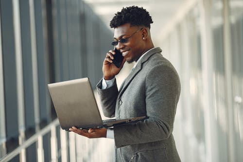 Side view of cheerful stylish black businessman in formal gray jacket and trendy sunglasses using laptop and having conversation via smartphone while standing in modern hallway