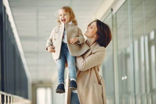 Excited mother and daughter standing in glass hallway