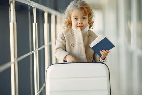 Cute little girl with suitcase and passport