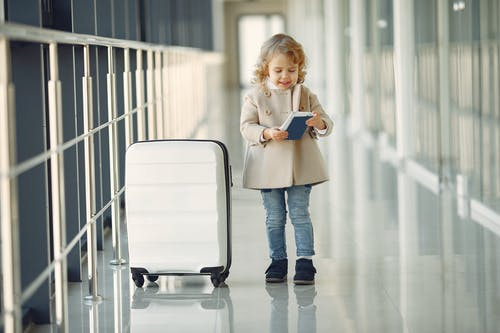 Full body of smiling cute little girl in jeans and beige coat standing near suitcase and checking information in documents