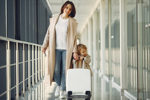 Positive mother and daughter with suitcase in airport corridor