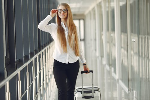 Positive smiling young female with long blond hair in formal outfit touching eyeglasses and carrying suitcase while walking along airport corridor