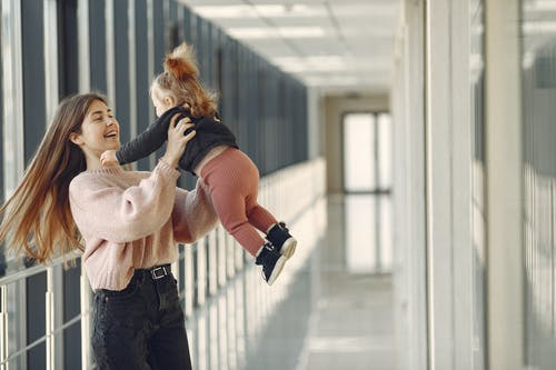 Cheerful young woman in casual outfit smiling and spinning around cute little girl while standing in modern building corridor in daylight