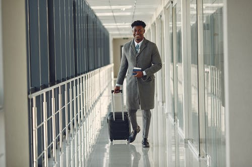 Stylish man with suitcase and passport walking along airport corridor