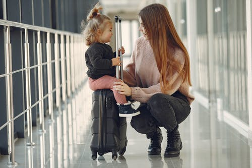 Full length of positive content woman and cute stylish blond little girl sitting on black suitcase in airport corridor while waiting for flight