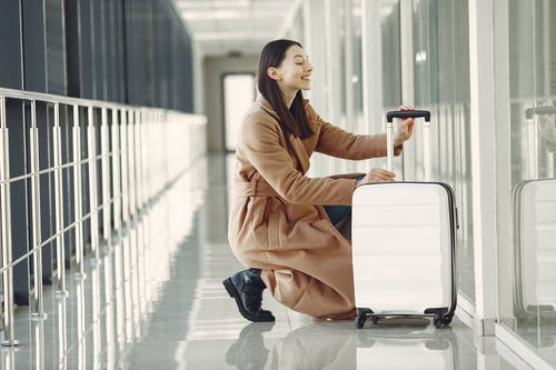 Excited woman with luggage in airport