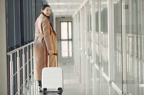 Stylish happy traveler with suitcase in airport hallway