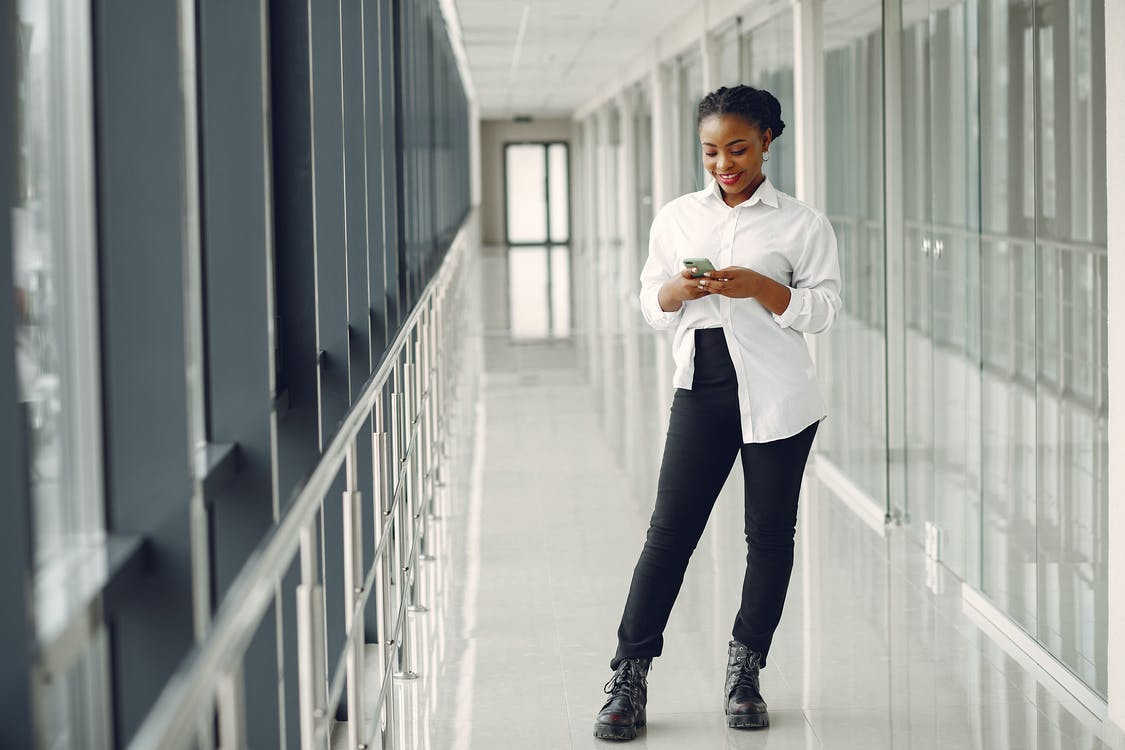 Full length of optimistic positive African American female office worker in formal clothes text messaging on cellphone while standing in modern office building