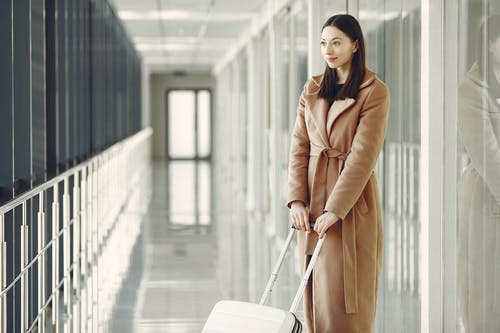 Content woman with suitcase waiting for boarding in airport