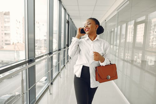 Cheerful woman talking on smartphone in modern office building