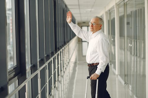 Senior man waving goodbye and walking in airport corridor