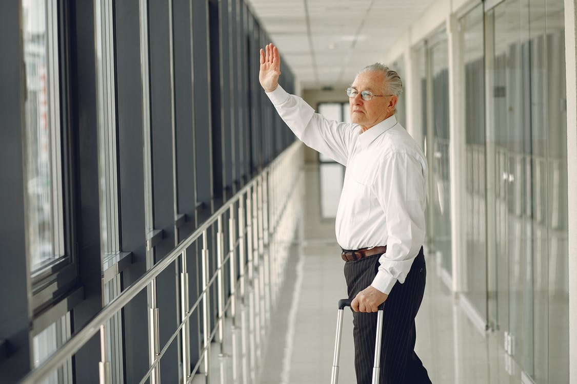 Side view of aged calm male in formal clothes with suitcase walking along modern airport hallway and waving goodbye while looking out glass wall