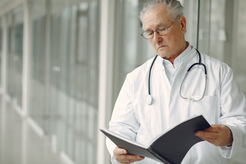 A doctor in uniform reading clinical records.   Photo: Pexels