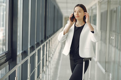 Positive young businesswoman in stylish formal wear with suitcase talking on smartphone and standing in modern airport corridor while waiting for flight