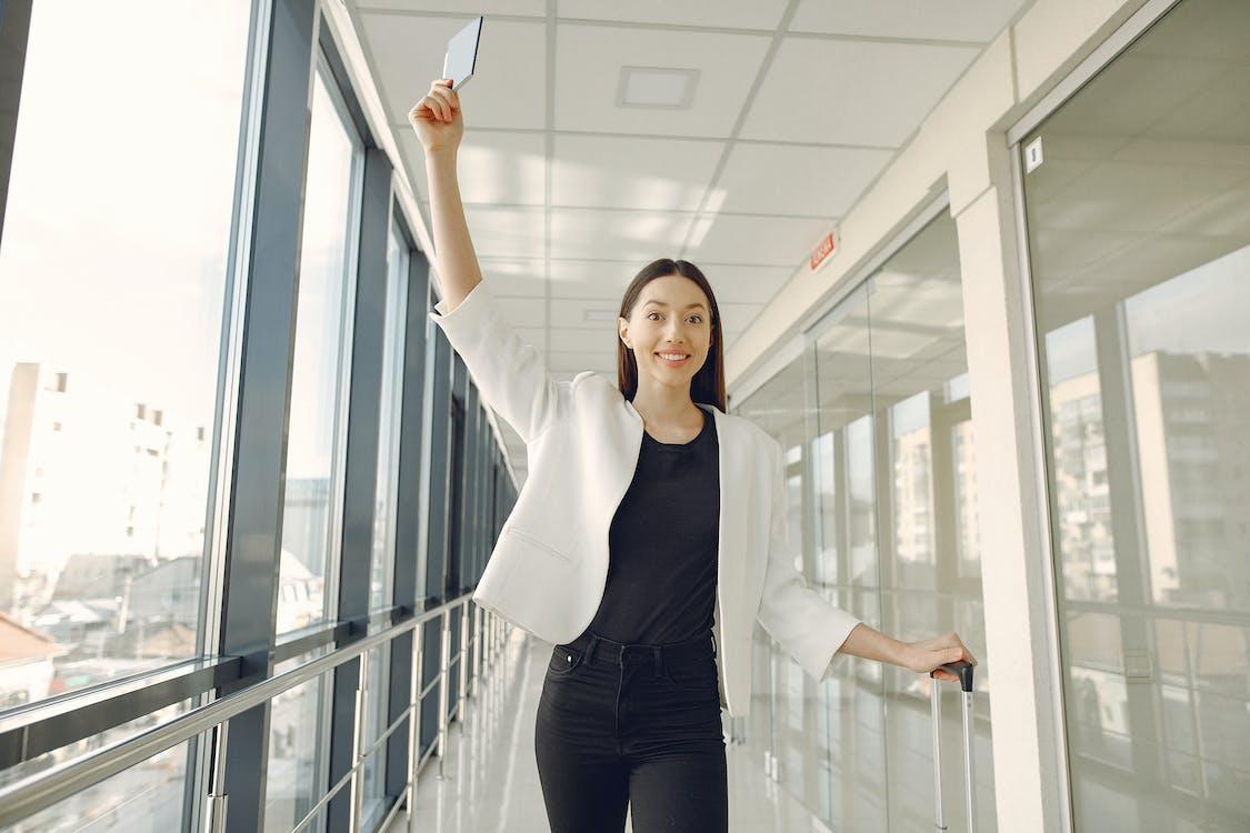Smiling woman showing passport in modern corridor